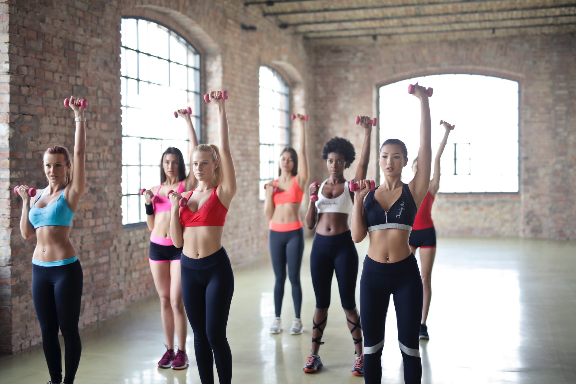 women having exercise using dumbbells
